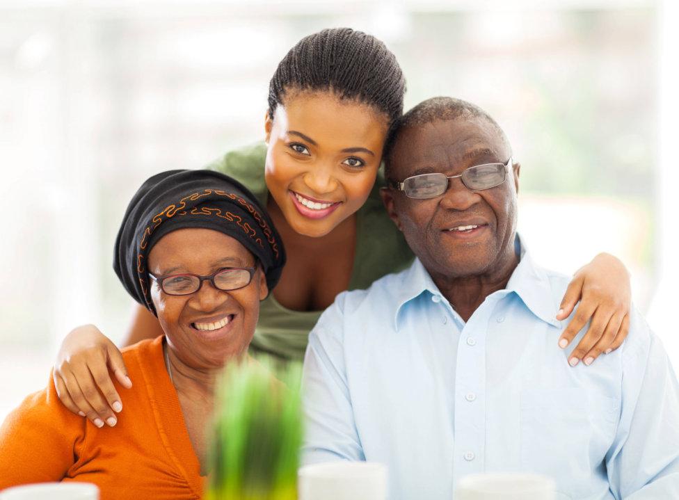 caregiver and senior couple smiling