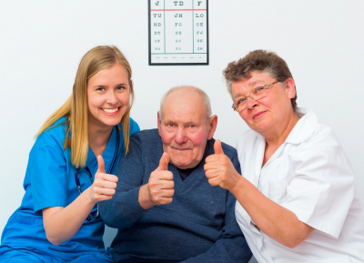old man showing thumbs up with his caregiver